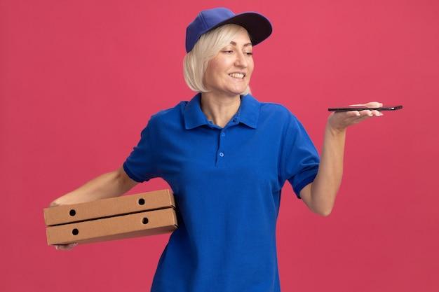 Mulher loira de meia-idade, sorridente, entregadora de uniforme azul e boné, segurando pacotes de pizza e o celular olhando para o telefone