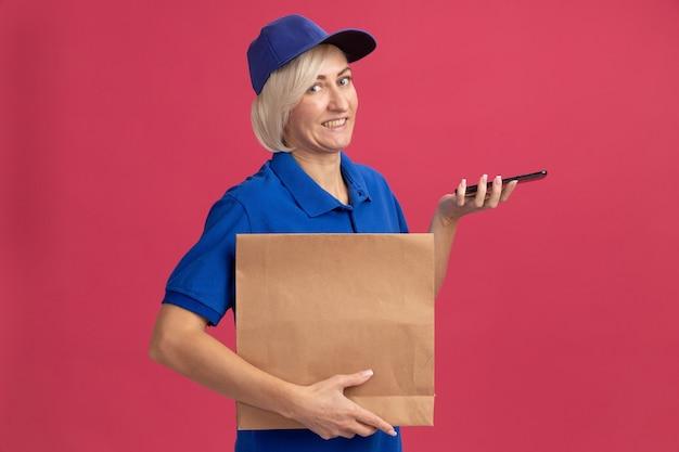 Mulher loira de meia-idade sorridente, entregadora de uniforme azul e boné, segurando um pacote de papel e um telefone celular