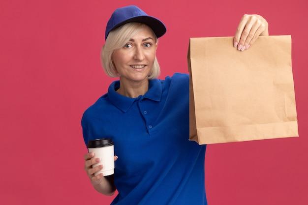 Mulher loira de meia-idade sorridente, entregadora de uniforme azul e boné, segurando uma xícara de café de plástico e um pacote de papel