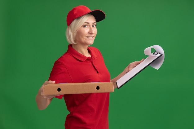 Mulher loira de meia-idade sorridente, entregadora de uniforme e boné vermelhos