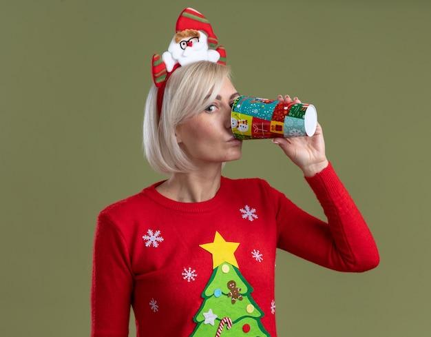 Mulher loira de meia-idade usando bandana de papai noel e suéter de natal olhando para a câmera, bebendo café em uma xícara de café de natal de plástico isolada em fundo verde oliva