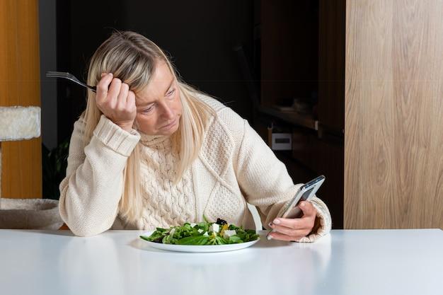Mulher loira de meia-idade usando smartphone enquanto come salada na cozinha, conceito de estilo de vida