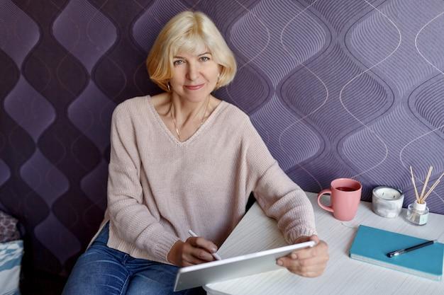 Mulher loira de meia idade usando tablet