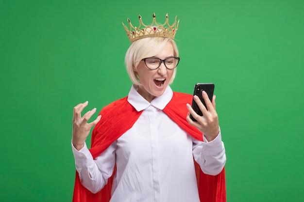 Mulher loira de meia-idade zangada, super-heroína com capa vermelha usando óculos e uma coroa, segurando e olhando para o celular, mantendo a mão no ar isolada na parede verde com espaço de cópia