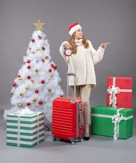 Mulher loira de natal com chapéu de papai noel segurando um despertador vermelho perto da árvore branca de natal