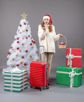 Mulher loira de natal com chapéu de papai noel segurando uma cesta de presentes perto da árvore de natal