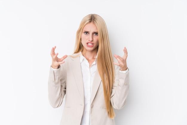 Mulher loira de negócios jovem em branco chateado gritando com mãos tensas.