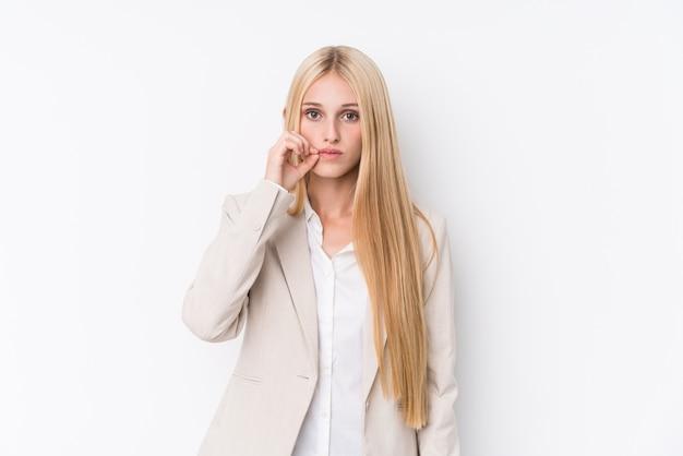 Mulher loira de negócios jovem em fundo branco com os dedos nos lábios, mantendo um segredo.