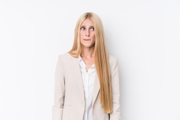 Mulher loira de negócios jovem em fundo branco confuso, sente-se duvidoso e inseguro.