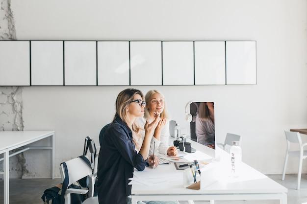 Mulher loira de óculos e camisa preta trabalhando na mesa com o computador e documentos nele