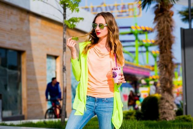 Mulher loira de óculos escuros com coquetel posando ao ar livre