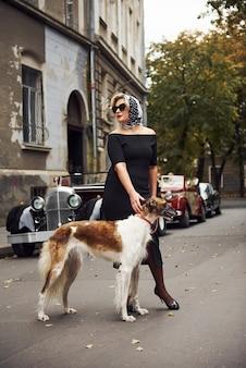 Mulher loira de óculos escuros e vestido preto perto de um carro clássico vintage com seu cachorro.