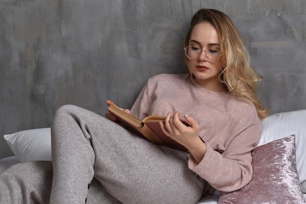 Mulher loira de óculos, roupas casuais. ela está reclinada na cama e lendo um livro no quarto em casa. estudante, blogueiro, estudo de documentos. interior com parede cinza, almofadas rosa e brancas. fechar-se