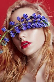 Mulher loira de retrato com pétalas de flores no rosto