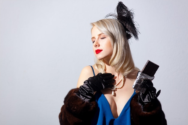 Mulher loira de vestido azul vintage e casaco de pele com barra de chocolate escura