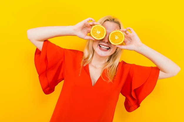 Mulher loira de vestido com laranjas