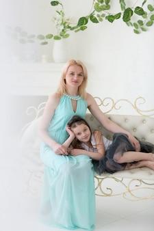 Mulher loira de vestido grego com a filha