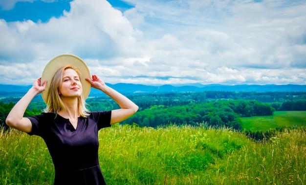 Mulher loira de vestido preto e chapéu branco em um prado com montanhas atrás