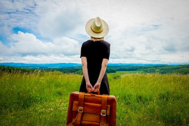 Mulher loira de vestido preto e mala no prado com montanhas atrás