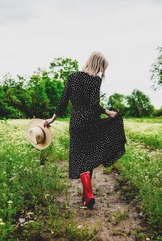 Mulher loira de vestido preto em campo de flores de camomila
