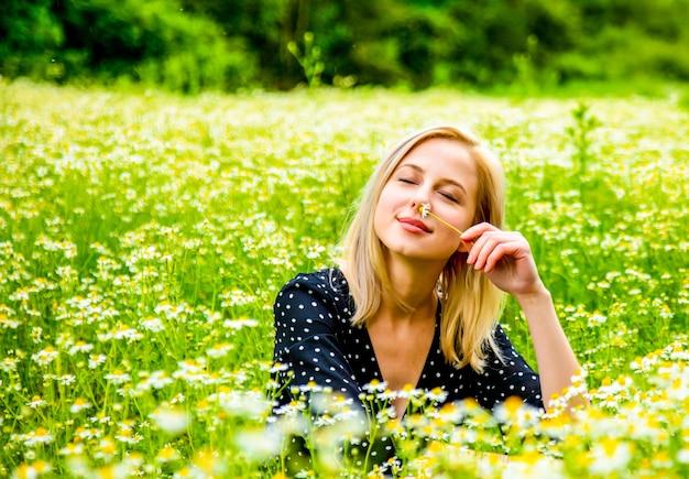 Mulher loira de vestido preto sentada no campo de flores de camomila