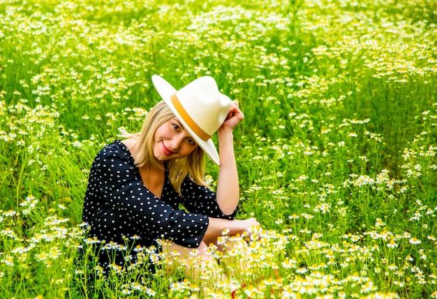 Mulher loira de vestido preto sentada no campo de flores de chamomiles