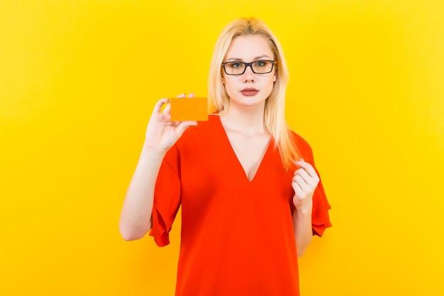 Mulher loira de vestido vermelho com cartão de crédito