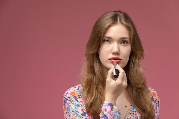 Mulher loira de visão frontal usando batom vermelho na parede rosa