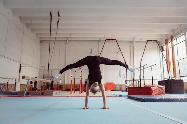 Mulher loira de visão traseira se exercitando para as olimpíadas de ginástica