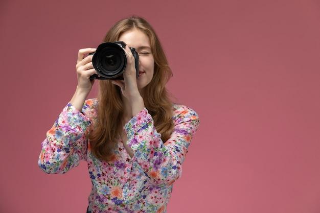 Mulher loira de vista frontal tirando uma foto de uma pessoa que está na frente dela