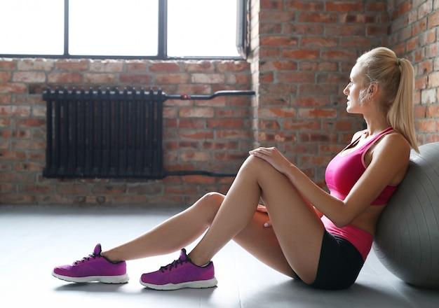 Mulher loira descansando após o exercício.