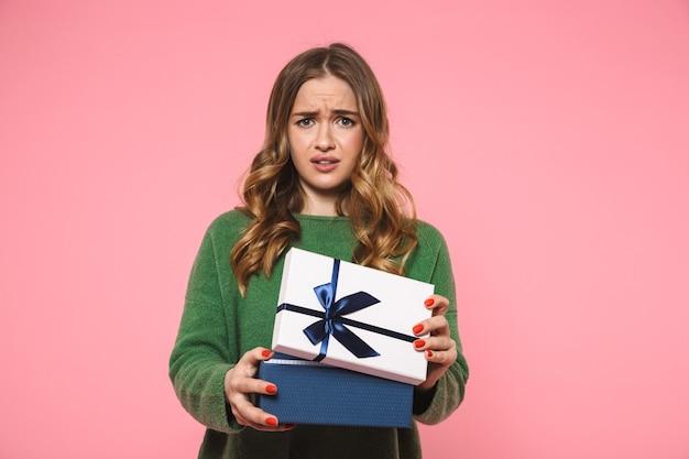 Mulher loira descontente vestindo um suéter verde abrindo uma caixa de presente e olhando para a frente sobre a parede rosa