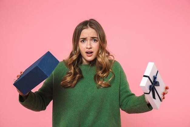 Mulher loira descontente vestindo um suéter verde abrindo uma caixa de presente vazia e olhando para a frente sobre a parede rosa