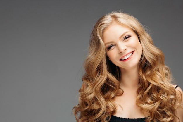 Mulher loira deslumbrante com penteado após a aparência de cabeleireiro
