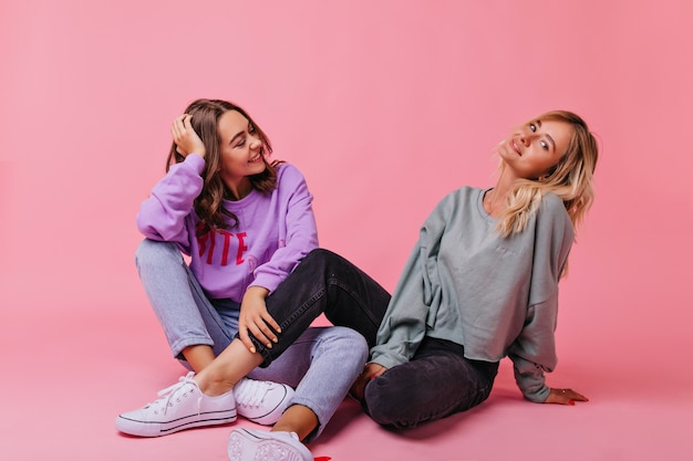 Mulher loira deslumbrante em calças pretas e sapatos brancos, sentada na rosa. irmãs fofas relaxadas posando no chão.