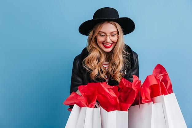 Mulher loira deslumbrante segurando sacolas de compras. garota da risada com chapéu elegante, posando na parede azul.