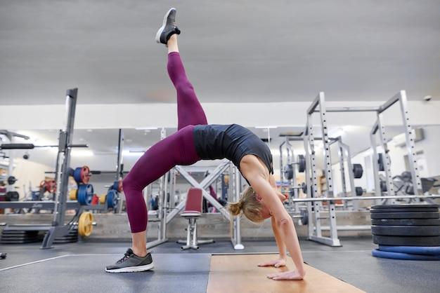 Mulher loira desportiva adulta que estica o corpo ao fazer exercícios de ioga na academia