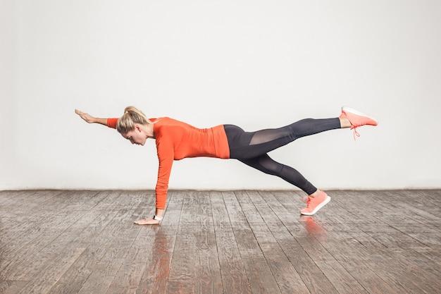 Mulher loira desportiva fazendo pland na sala interior do loft. foto de estúdio