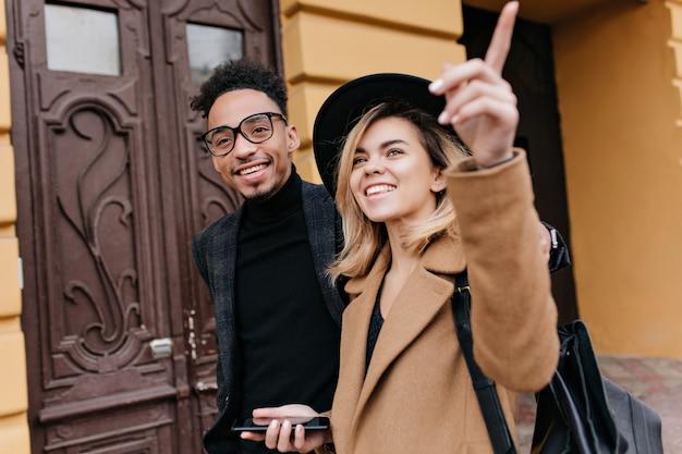 Mulher loira despreocupada com chapéu, mostrando ao amigo africano algo interessante. retrato ao ar livre do negro sorridente de óculos, andando pela cidade em um dia frio com uma senhora de cabelos louros.