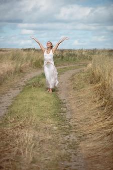 Mulher loira despreocupada em pé no caminho do campo