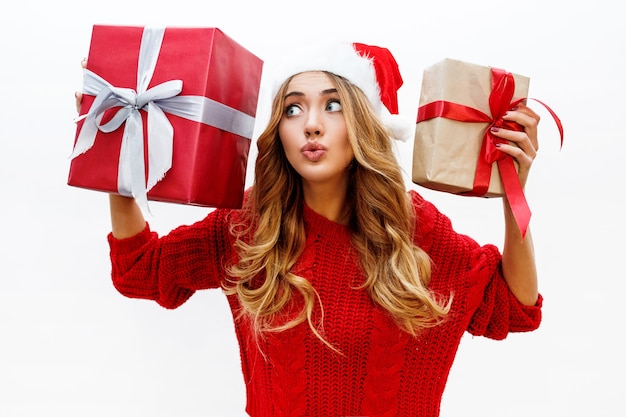 Mulher loira despreocupada feliz comemorando a festa de ano novo com presentes. usando chapéu de papai noel vermelho e blusa de malha. posando