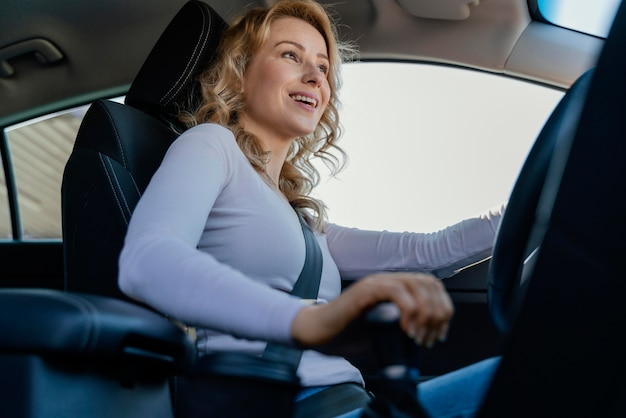 Mulher loira dirigindo o carro dela