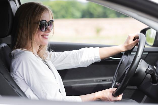 Mulher loira dirigindo um carro enquanto usava óculos