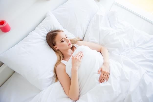 Mulher loira dormindo na cama dela
