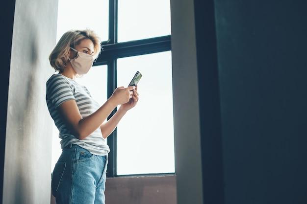 Mulher loira durante o bloqueio sentada perto da janela e conversando no celular usando máscara médica