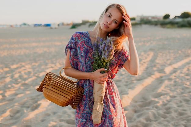 Mulher loira e bonita com buquê de lavanda, caminhando na praia. cores do sol.