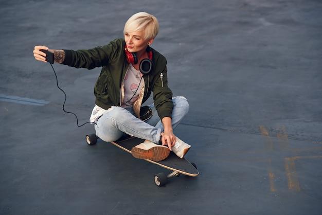 Mulher loira e bonita com fones de ouvido, fazendo auto foto no telefone enquanto está sentado no longboard ao pôr do sol.