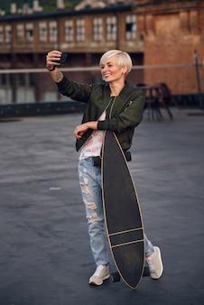 Mulher loira e bonita com longboard, fazendo auto foto telefone no telhado ao pôr do sol.