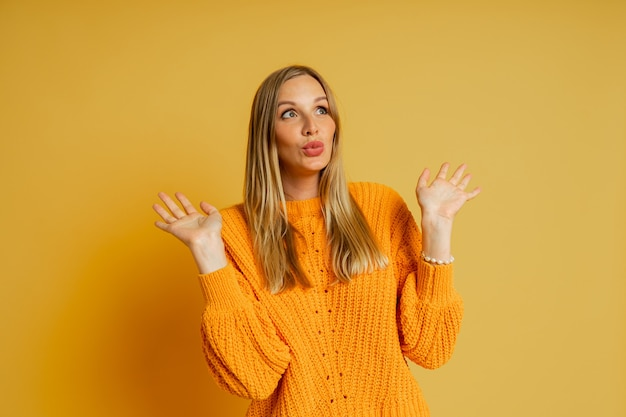 Mulher loira e bonita com rosto suprice em suéter laranja elegante de outono posando em amarelo.