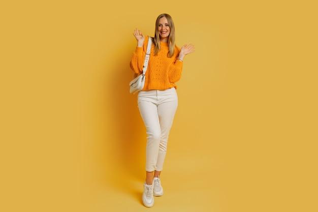 Mulher loira e bonita com roupa de outono na moda posando em amarelo. segurando uma bolsa de couro branco. toda a extensão.